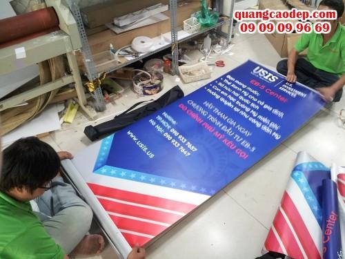 Nhân viên gia công của In Kỹ Thuật Số đang lắp banner cuốn cho poster đặt in từ khách hàng